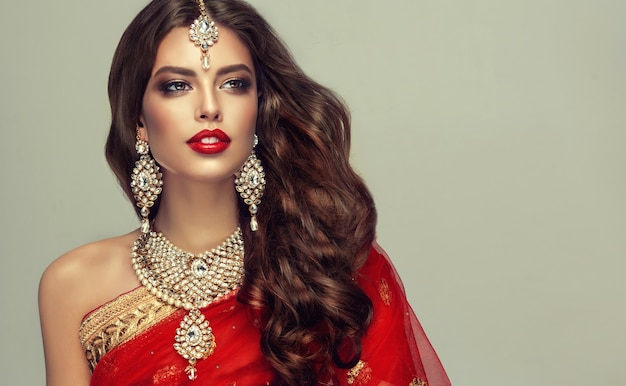 Young attractive woman, dressed in traditional indian red shawl (dupatta) and hand-made