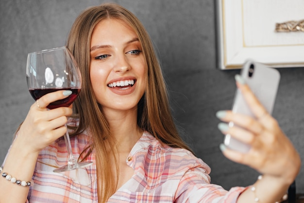 와인을 마시고 부엌에서 스마트 폰을 사용하는 젊은 매력적인 여자 초상화