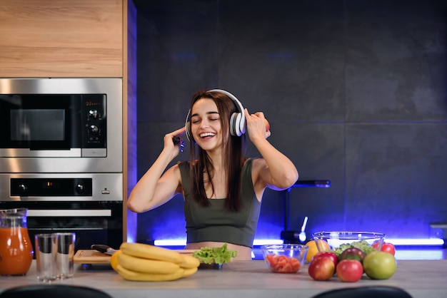 若い魅力的な女性は赤いリンゴを食べるし、朝のキッチンで音楽を聴きます。朝食を楽しんで健康的なライフスタイルのコンセプト。