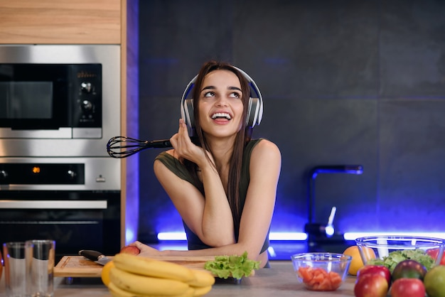 Young attractive woman eats red apple and listens to the music at kitchen in morning. healthy lifestyle concept, enjoying breakfast.