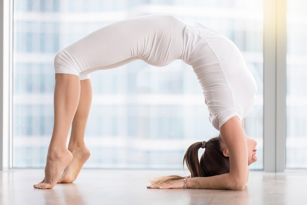 Young attractive woman in elbow bridge pose against floor window