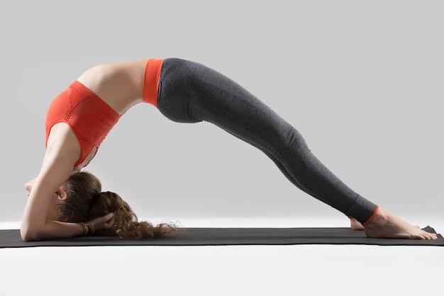 Young attractive woman in elbow bridge pose, grey studio backgro