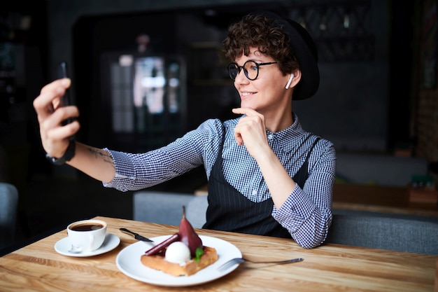 Young attractive woman in elegant casualwear and hat making selfie while relaxing in cafe and having dessert