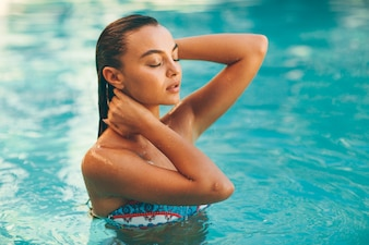 Young attractive woman enjoys in the outdoor swimming pool in summer time