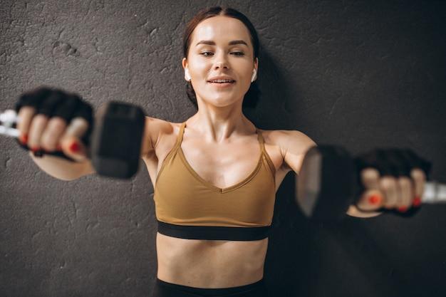 체육관에서 아령으로 운동하는 젊은 매력적인 여자