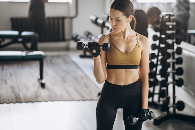 Young attractive woman exercising with dumbbells at the gym