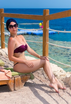 Young attractive woman in female turban and sunglasses sitting on sun lounger at exotic beach with golden sand and looking at the camera