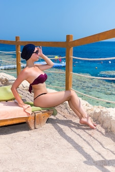 Young attractive woman in female turban and sunglasses sitting on sun lounger at exotic beach with golden sand and looking at the sea with corals and reefs against blue sky