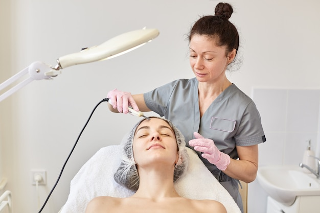 Young attractive woman getting ultrasonic facial skin cleansing treatment by professional cosmetologist