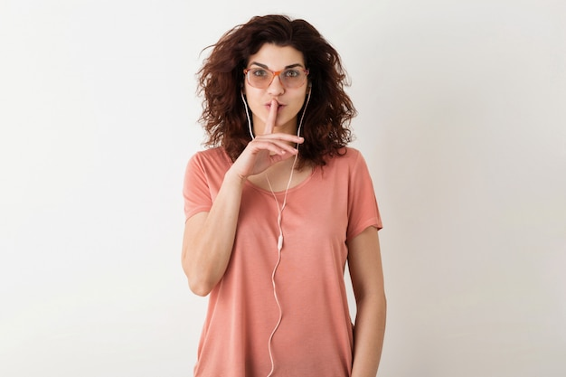 Young attractive woman in glasses listening to music on earphones, holding finger at lips, showing silence gesture, funny surprised emotion, curly hair, isolated, pink t-shirt