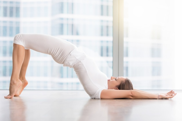 Young attractive woman in glute bridge pose