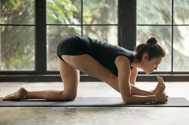 Young attractive woman in half splits pose, studio background