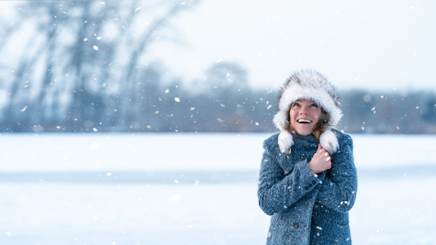 Young attractive woman happy with the falling snow in winter nature