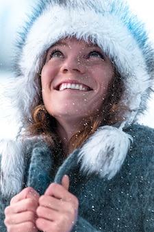 Молодая привлекательная женщина счастлива с падающим снегом в зимней природе