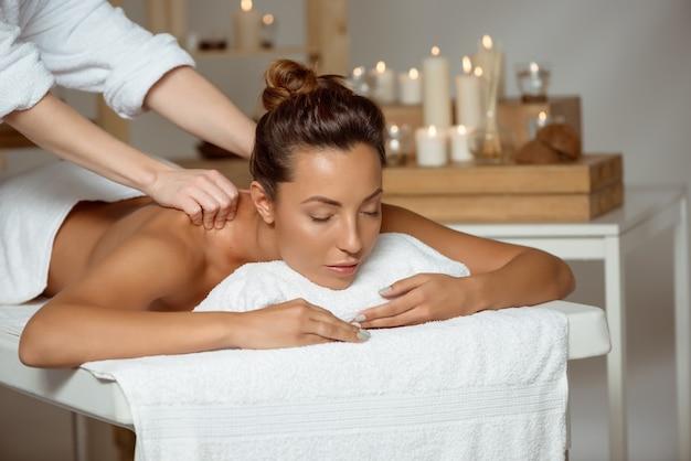 Молодая привлекательная женщина имея массаж ослабляя в салоне спы.