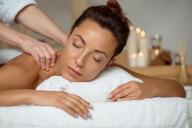 Giovane donna attraente con massaggio rilassante nel salone spa.