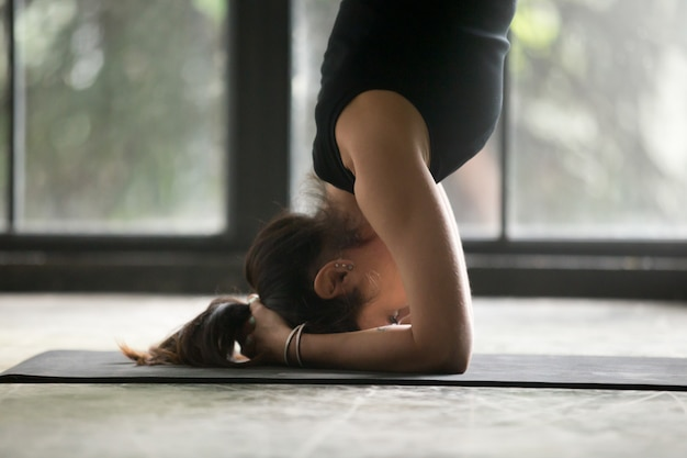 Young attractive woman in headstand pose, close up