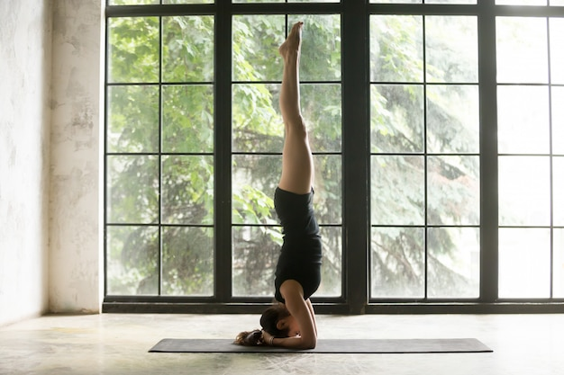Young attractive woman in headstand pose, studio background
