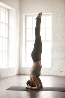 Young attractive woman in headstand pose, white loft studio