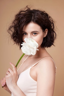 Молодая привлекательная женщина прячет лицо за цветком