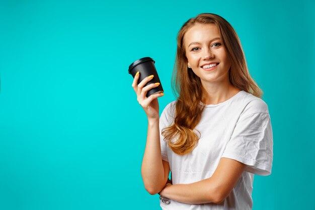 ホットドリンクのカップを保持している若い魅力的な女性
