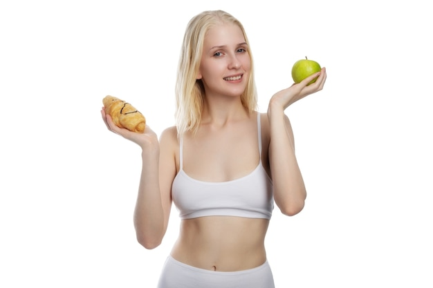 Young attractive woman holding apple and cake in hands in a healthy versus tasty