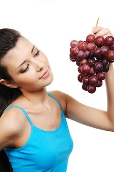 Giovane donna attraente che tiene un grappolo d'uva
