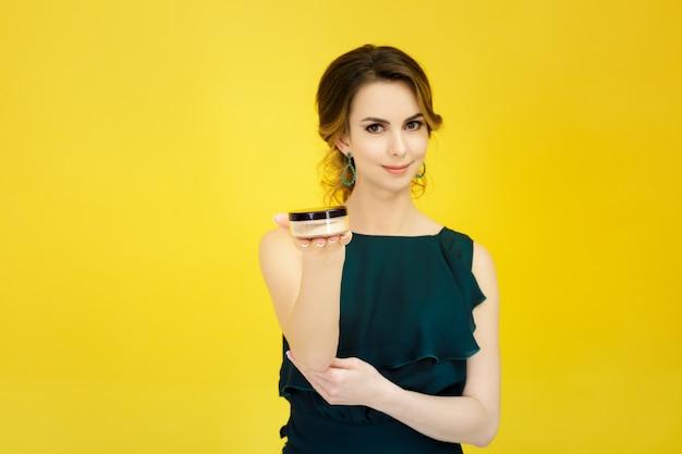 黄色の背景にフェイスパウダーを保持している若い魅力的な女性
