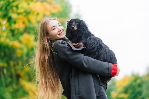 秋の公園で日の出の屋外で彼女の腕にダックスフント犬を保持している若い魅力的な女性
