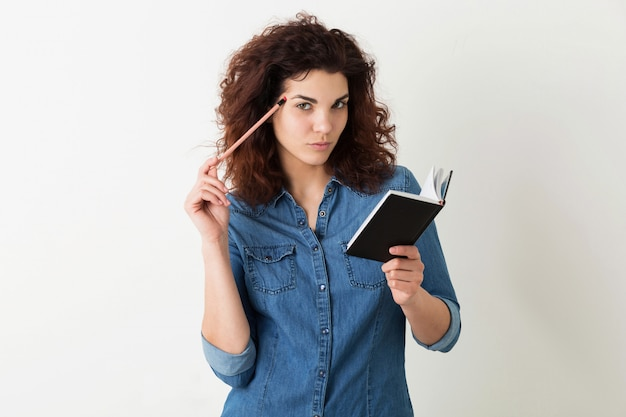 Young attractive woman holding notebook and pencil, thinking, seriuous face expression, curly hair, pensive, isolated, denim blue shirt, student learning, education