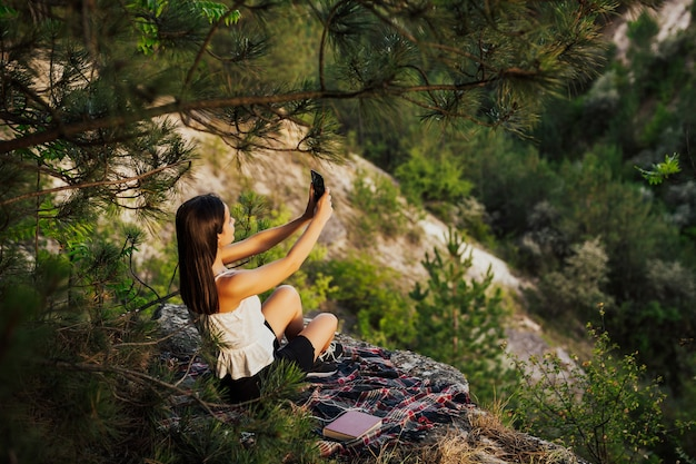 Young attractive woman holding a smartphone and taking a selfie on the rock, above the valley with perfect pine forest.