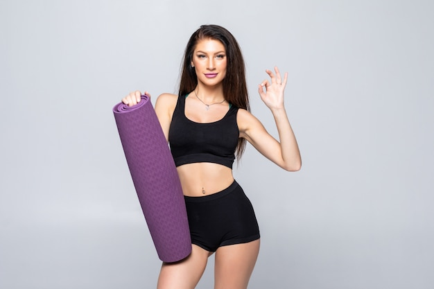 Young attractive woman holding a yoga mat isolated