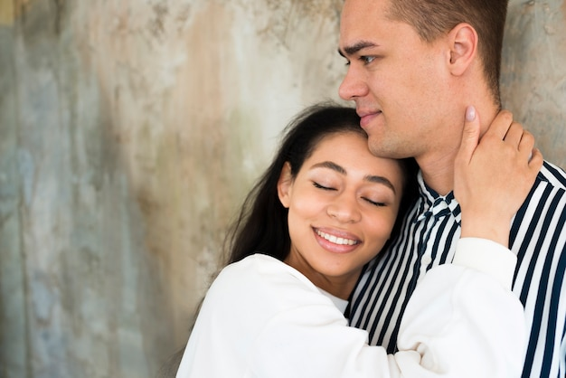 Young attractive woman hugging boyfriend against concrete wall