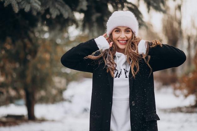Молодая привлекательная женщина в зимнем парке в милой шляпе