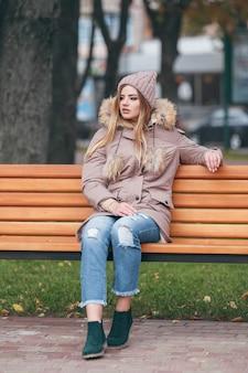 秋の服を着た若い魅力的な女性は、都市公園のベンチに座っています。
