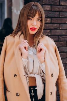 거리에서 포즈를 취하는 베이지 색 코트에 젊은 매력적인 여자
