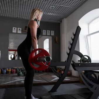 운동화에 검은 운동복에 젊은 매력적인 여자는 체육관에서 훈련에 바벨을 올립니다