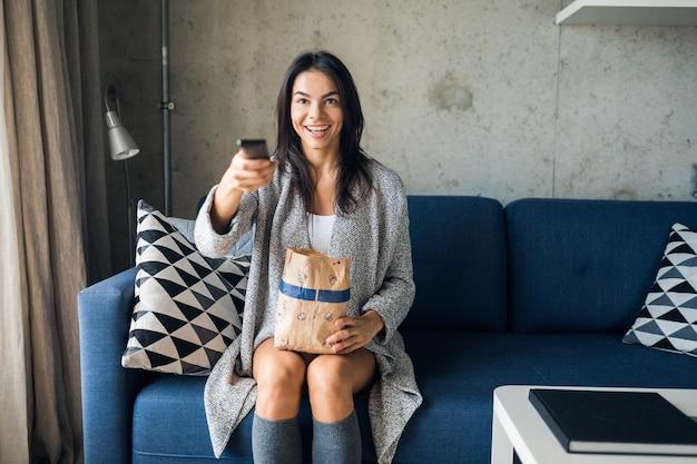 Молодая привлекательная женщина в повседневной одежде отдыхает дома, смотрит фильмы по телевизору, держит пульт, переключает каналы, ест попкорн, отдыхает, веселится, улыбается, сидя на диване, веселая, счастливая
