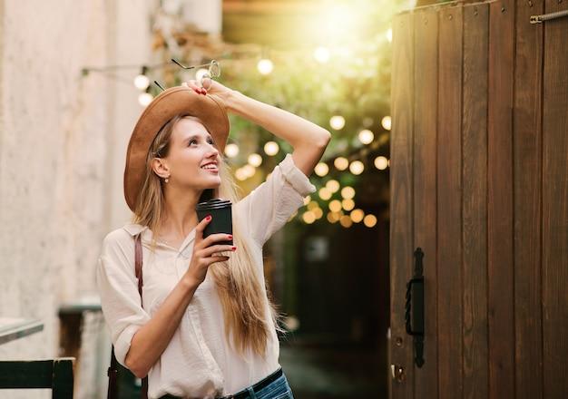 外出先でコーヒーを飲みながら旧市街の中庭を歩いているカジュアルなスタイルの服を着た若い魅力的な女性