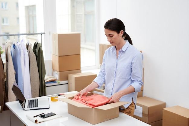 Молодая привлекательная женщина в повседневной одежде кладет сложенный красный пуловер в коробку, упаковывая заказ клиента интернет-магазина