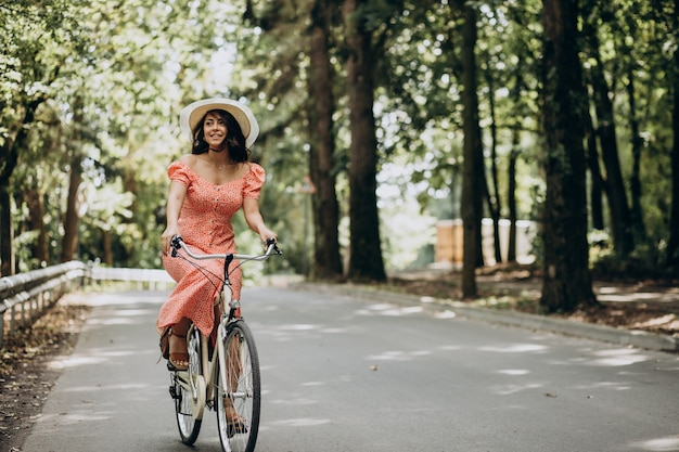 Молодая привлекательная женщина в платье, езда на велосипеде