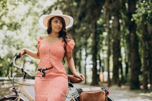 自転車に乗ってドレスの若い魅力的な女性