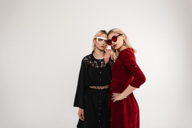 Молодая привлекательная женщина в модном черном платье в очках обнимает сестру-близнеца в модном красном платье в модных солнцезащитных очках возле винтажной стены в комнате