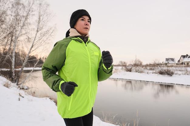 冬の海岸に沿ってジョギングする緑のジャケットと手袋の若い魅力的な女性