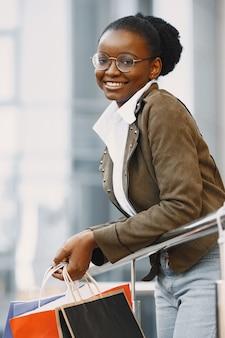 ジャケットを着て、たくさんのショッピングパッケージを持って、通りを歩いている若い魅力的な女性。ショッピングのコンセプト