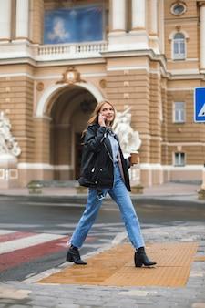가죽 재킷과 청바지에 커피 한잔 들고 젊은 매력적인 여자가 손에 들고 핸드폰으로 이야기하고 꿈꾸게 아늑한 도시 거리를 걷는 동안