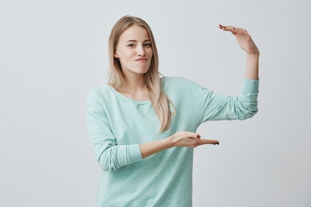 身振りで示す、手で大きな何かを示す光の青いセーターの若い魅力的な女性。
