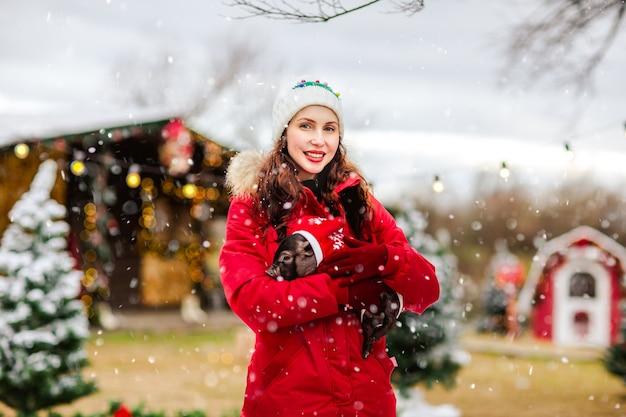 Молодая привлекательная женщина в красных зимних комбинезонах и белой шляпе позирует с маленькой черной свиньей на фоне рождества.