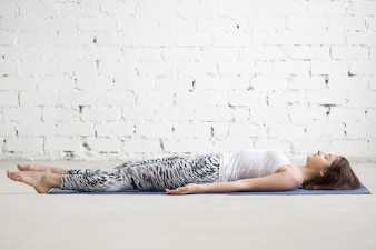 Young attractive woman in Savasana pose, white studio background
