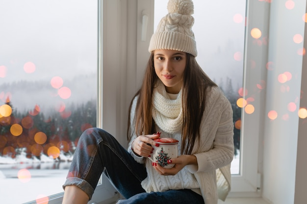 スタイリッシュな白いニットのセーター、スカーフと帽子の若い魅力的な女性がクリスマスに窓辺に座って熱いお茶を飲むカップ、冬の森の背景ビュー、ライトボケ